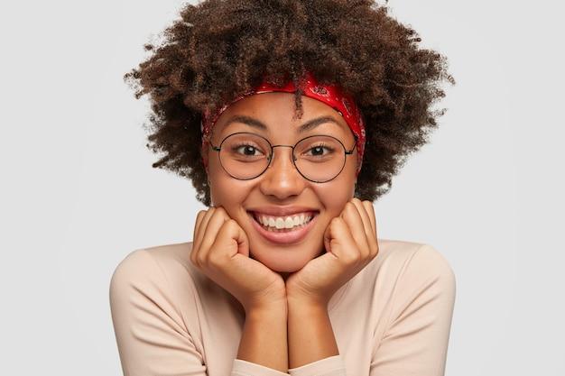 Close up portrait of happy black lady tient le menton à deux mains, heureux que tout va bien, porte des lunettes rondes, a les cheveux bouclés, écoute une histoire drôle de l'interlocuteur. concept d'émotions positives