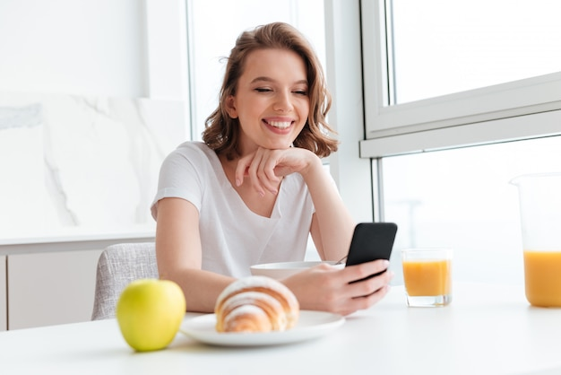 Close-up portrait of happy brunette woman using mobile phone while having breakfast at white kitchen