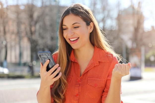 Close up portrait of happy happy girl satisfait de lire de bonnes nouvelles sur téléphone mobile et célébrer avec le poing dans la rue de la ville
