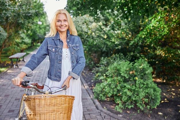 Close up portrait of happy happy lady en veste en jean et robe blanche tenant un guidon d'un vélo de ville avec panier