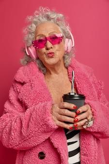 Close up portrait of happy mamie à la mode ridée portant des collants roses et manteau