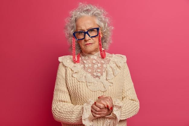 Close up portrait of happy mamie à la mode ridée portant des lunettes et un pull