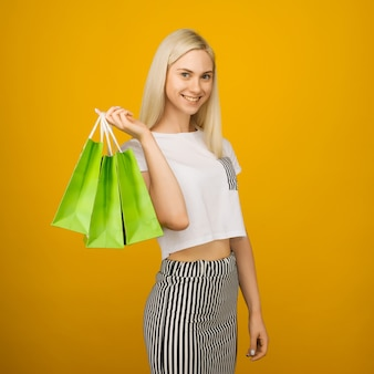 Close-up portrait of happy young beautiful blonde woman holding green shopping bags, looking at camera, sur jaune