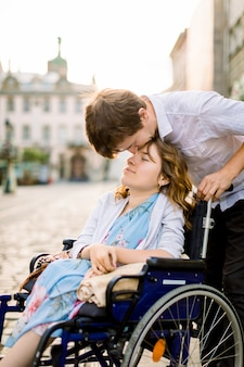 Close-up portrait of happy young woman in wheelchair and her mari kissing her front, walking outdoors in old city