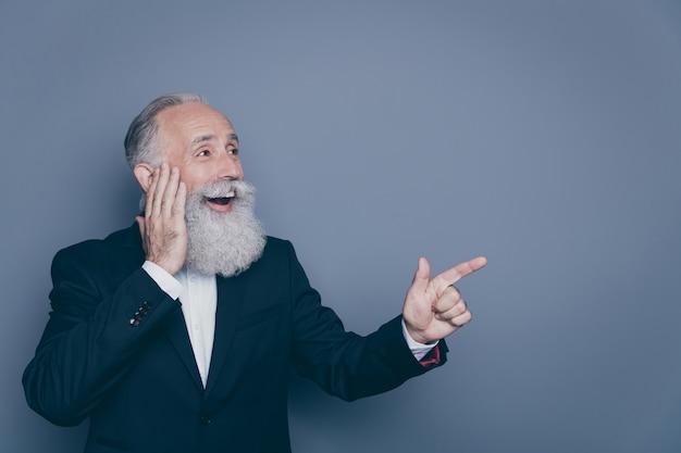 Close-up portrait of his he nice attrayant joyeux joyeux étonné étonné étonné homme aux cheveux gris pointant l'index de côté copie espace isolé sur fond de couleur pastel violet gris
