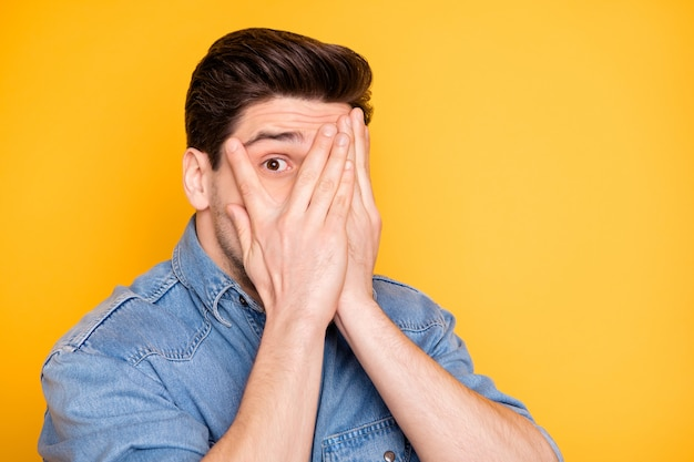Close-up portrait of his il nice attrayant beau funky drôle enfantin gars se cachant le visage derrière les paumes en évitant de jeter un œil isolé sur un mur de couleur jaune vif brillant vif