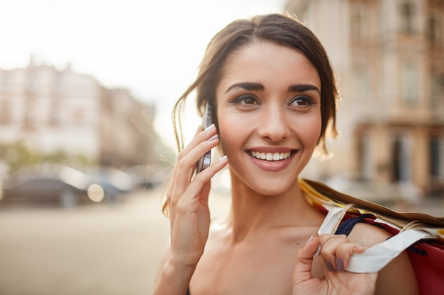 Close up portrait of joyful young caucasian woman with dark hair smiling with tooth, looking apart with happy and calm face expression, talking on phone with friend, holding shopping bags in