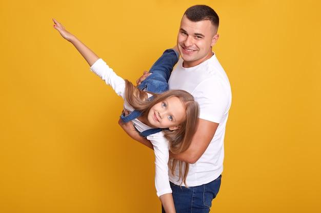 Close up portrait of kid jouant avec son papa, fille étant sur les mains du père, fait semblant de voler, écarte les bras sur le côté