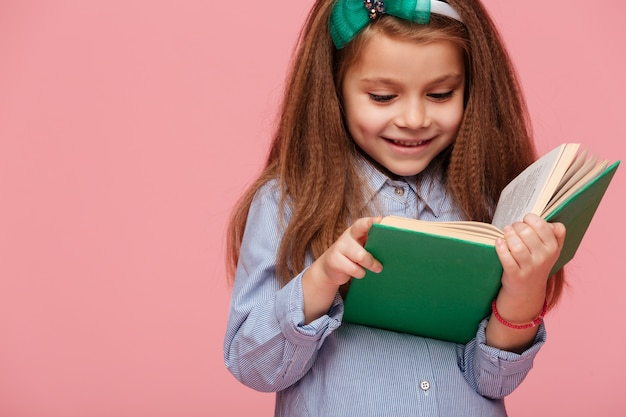 Close up portrait of lovely schoolgirl with long brown hair reading intéressante livre ayant des émotions heureuses