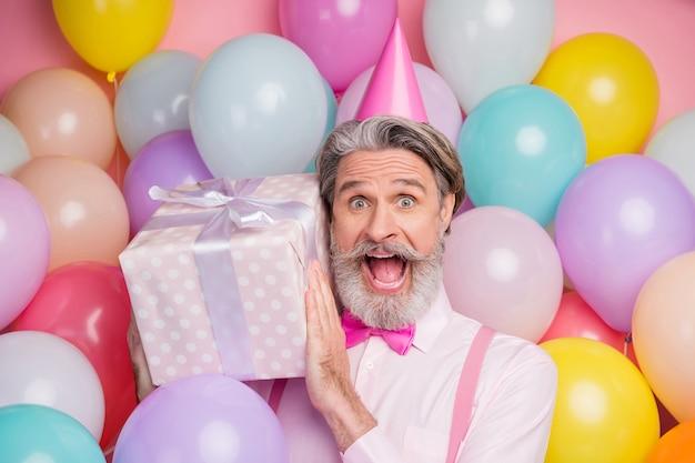 Close-up portrait of man holding in hands giftbox isolé sur fond de ballon rose