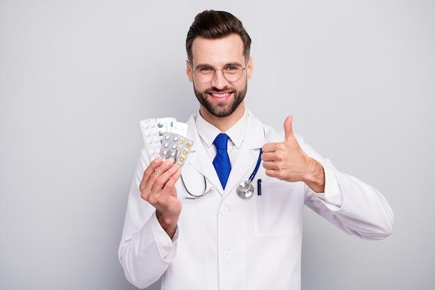 Close-up portrait of nice attrayant joyeux joyeux doc tenant dans les mains des plaques de pilules excellent traitement thérapeutique effet positif montrant thumbup isolé sur couleur pastel gris blanc clair