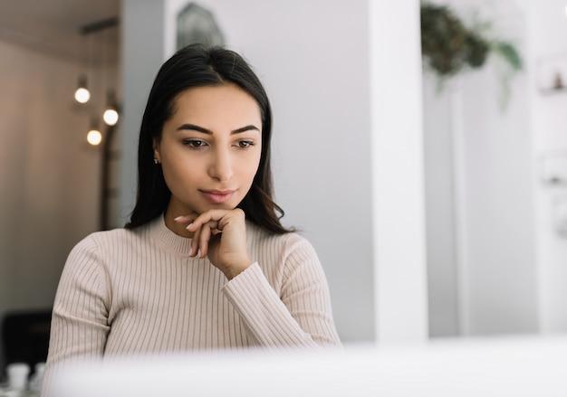 Close up portrait of pensive indian woman using laptop, regarder des cours de formation en ligne. pigiste asiatique travaillant à domicile