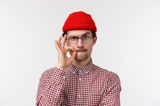 Close-up portrait of serious young caucasian guy with moustache, portez des lunettes et un bonnet, scellez les lèvres avec un geste du doigt comme si vous cachez le secret, promettez de ne pas en parler, debout