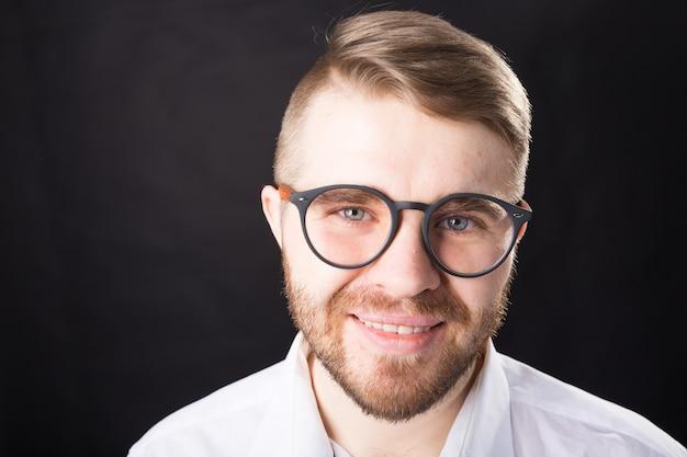 Close up portrait of smiling bel homme barbu dans des lunettes élégantes debout contre le mur noir