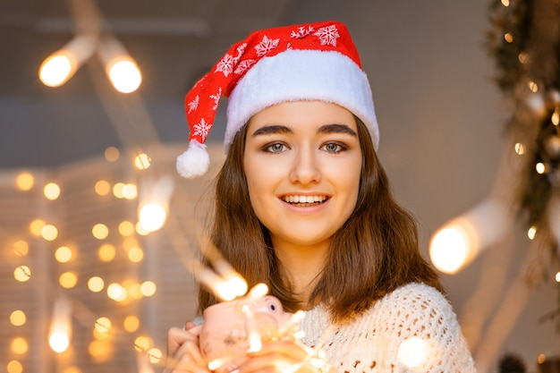 Close-up portrait of a smiling cute young woman with a santa hat on her head with garlands in her hands