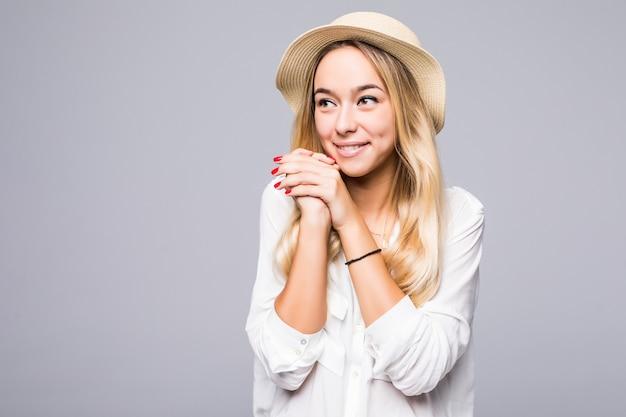 Close up portrait of a smiling young woman in hat en détournant les yeux à l'espace de copie isolé sur mur gris