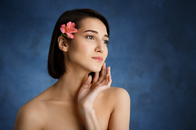 Close up portrait of tender young woman with pink flower in hair over blue wall