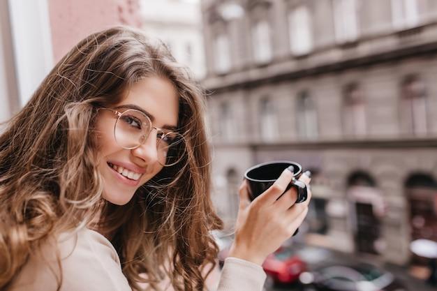 Close-up portrait of wonderful woman holding cup of latte sur fond de ville flou et à la recherche d'appareil photo