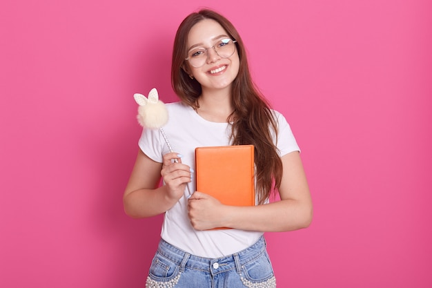 Close up portrait of young attractive woman holding her notebook isolé sur rose