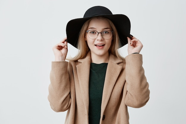 Close-up portrait of young blonde girl with pure skin, eyeglasses and smile wearing black hat and coat isolated. jolie femme appréciant son style.