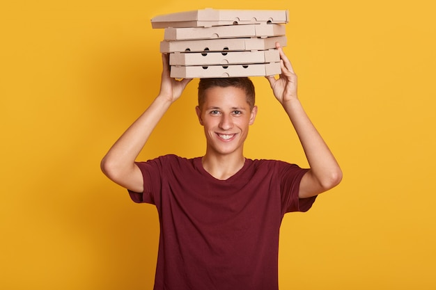 Close up portrait of young cheerful delivery man with red t-shirt standing, holding stack of cardboard pizza boxes on gray wall.