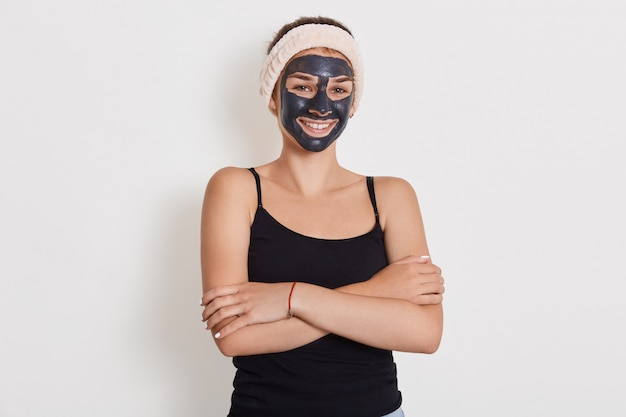Close up portrait of young female applique un masque d'argile du visage fait maison, a un bandeau blanc autour de la tête, sourit joyeusement, garde les mains jointes contre le mur blanc