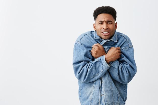 Close up portrait of young funny dark-skinned male with afro hairstyle in casual denim survêtement étant gelé en attendant un ami à l'extérieur en hiver. saison froide.