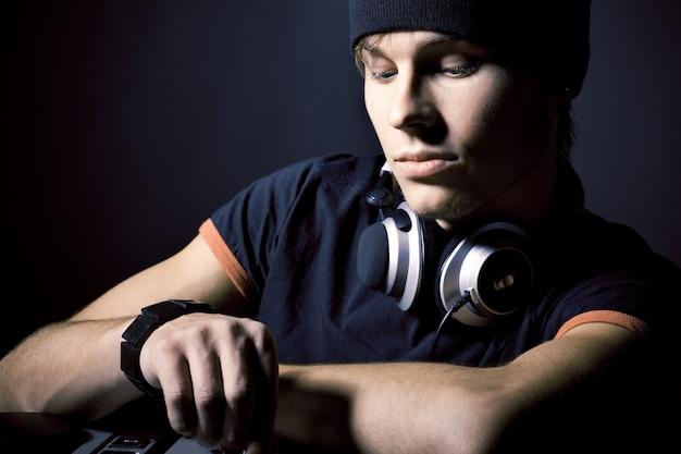 Close-up portrait of young man dj élégant avec un casque et un équipement musical