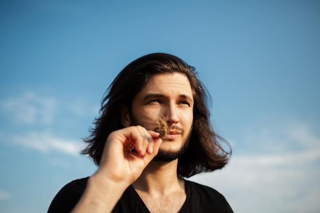 Close-up portrait of young man with long hair holding épi de blé dans la bouche.
