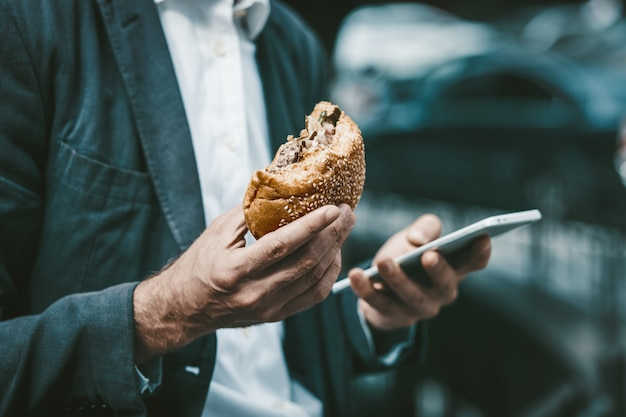 Close up portrait of a young white colar eating junk food while working on smartphone outdoors