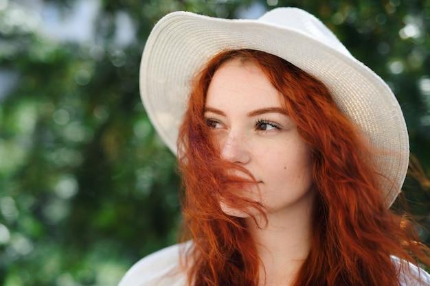 Close-up portrait of young woman with hat à l'extérieur de la ville, headshot.