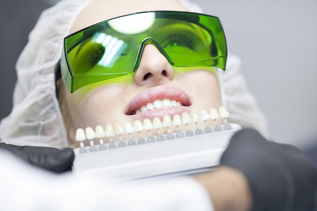 Close up portrait of young women in dentist chair, vérifiez et sélectionnez la couleur des dents. le dentiste fait le processus de traitement dans le bureau de la clinique dentaire.