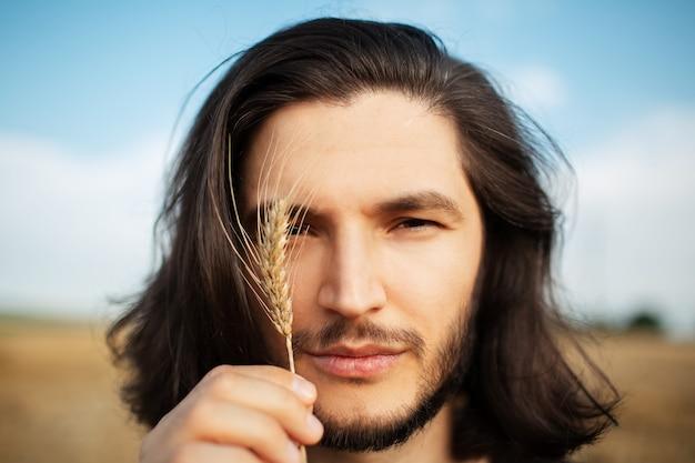 Close-up portrait en plein air de beau mec aux cheveux longs, tenant un épi de blé.