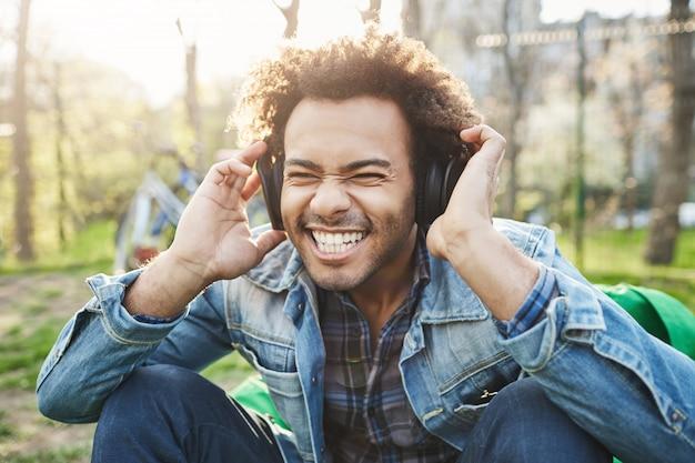 Close-up portrait en plein air de bel homme africain avec coupe de cheveux afro tenant la main sur le casque tout en écoutant de la musique et en étant excité, assis dans le parc.