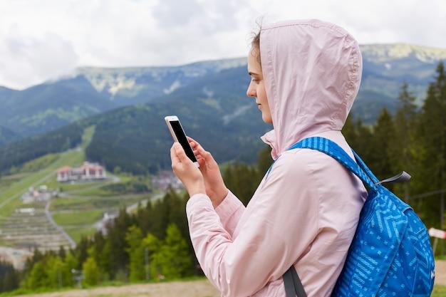 Close up portrait de profil de randonneur jeune femme avec sac à dos bleu à l'aide de smartphone dans un beau paysage de montagne au printemps