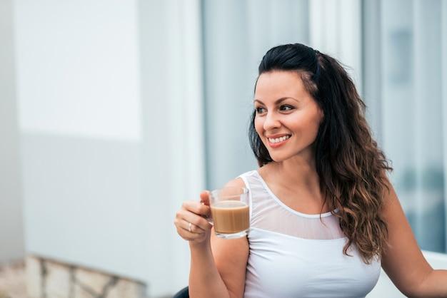Close-up portrait de souriante jeune femme avec un verre.