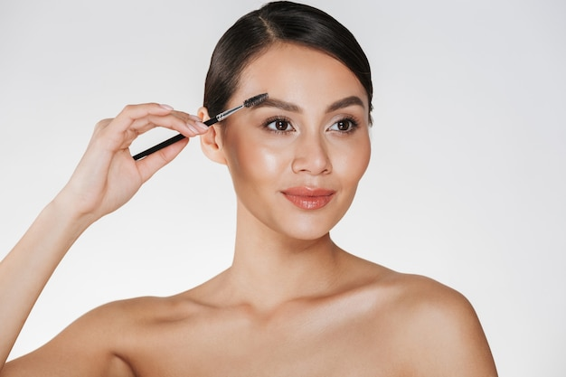 Close up portrait en studio de la belle femme brune à la peau douce peignant ses sourcils avec un pinceau de maquillage, isolé sur blanc