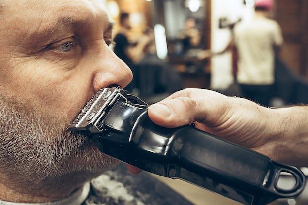 Close-up portrait de vue de côté de bel homme caucasien barbu senior se toilettage de barbe dans un salon de coiffure moderne.