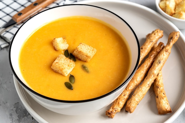 Close up de potiron, soupe à la crème de carottes dans un bol. avec croûtons, graines de citrouille et bâtonnets de pain.
