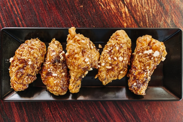 Close up de poulet frit coréen croustillant fait maison servi sur un long plat noir.