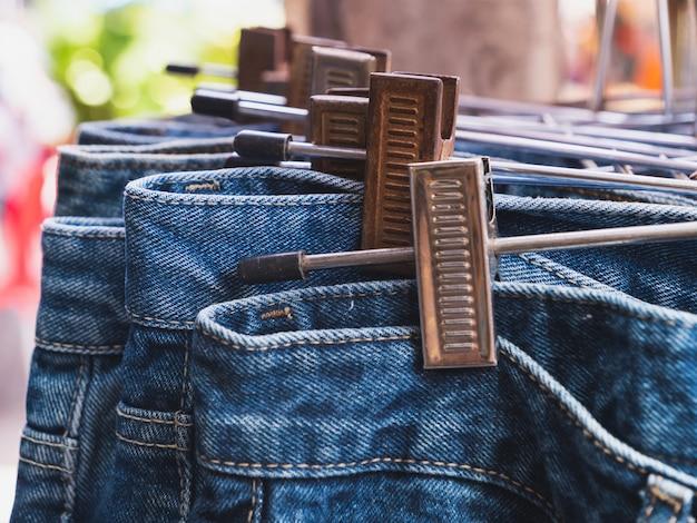 Close up rangée de nombreux blue jeans sont suspendus