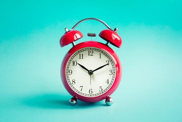 Close up réveil rouge sur fond pastel bleu.
