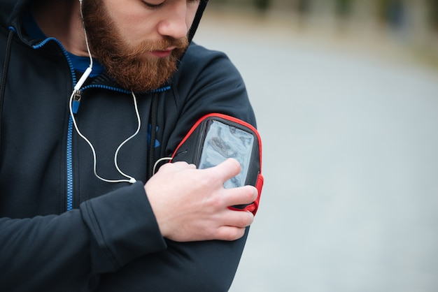 Close up runner avec parc de téléphone en regardant le téléphone