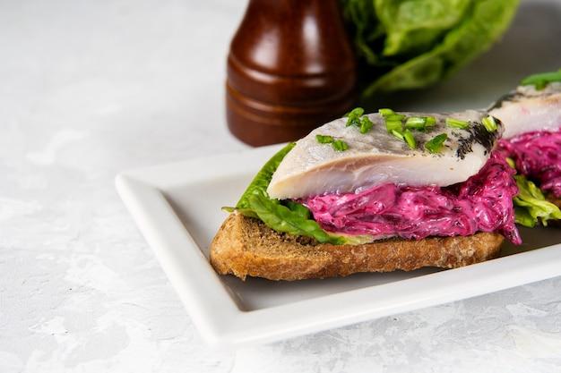 Close up de sandwich au hareng avec betterave et salade verte