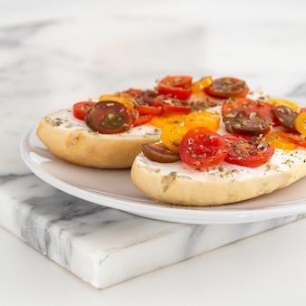 Close-up sandwiches au fromage à la crème et tomates cerises sur plaque
