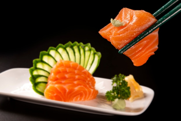 Close up sashimi de saumon au saumon dans une assiette blanche sans mise au point. sur fond noir