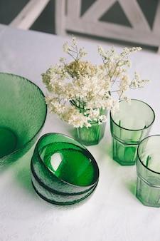 Close-up servant des plats sur une table. plats verts - saladier, assiettes creuses et verres. ils sont décorés d'un petit bouquet de fleurs