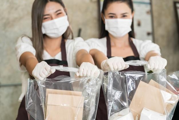 Close up serveuse porter un masque protecteur sourire et tenir le sac à provisions pour emporter ou plats à emporter.
