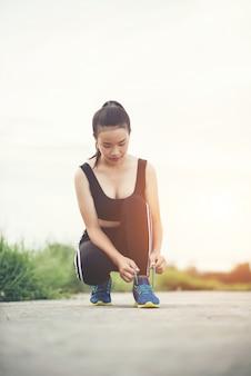 Close up shoes femme coureur attachant ses chaussures pour un exercice de jogging