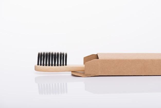 Close-up side profile view photo de eco-friendly emballé dans une brosse à dents en papier carton recyclé noir isolé sur fond blanc